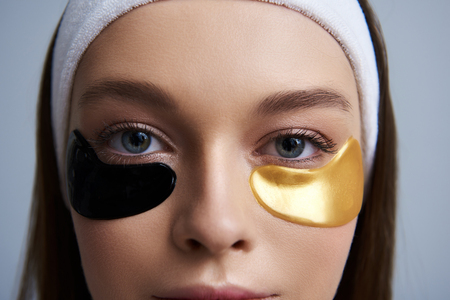 Confident glance. Close up of girl with multicolored masks under lower eyelids looking at camera
