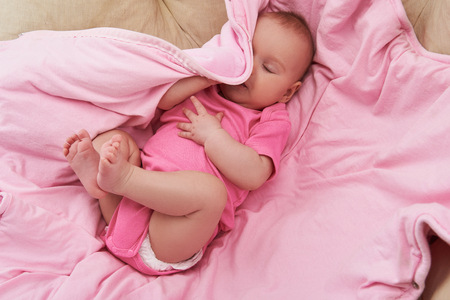 High angle top view photo of lovely and sweet newborn baby lying at comfort bad covering at soft blanket