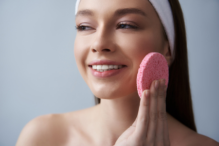 Close up portrait of attractive brunette girl in white headband cleaning cheek with soft exfoliating pad. Isolated on blue background Stock Photo