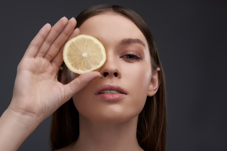 Close up portrait of beautiful young woman hiding eye behind slice of citrus while looking at camera and keeping mouth slightly open. Isolated on gray background