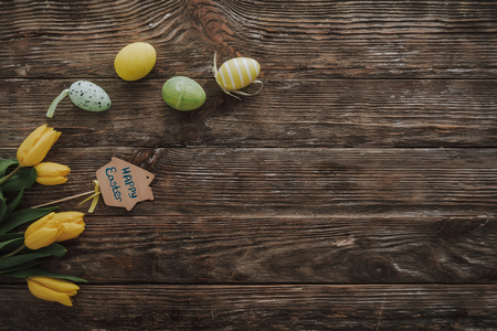 Preparing for Holly holiday. Top view of Easter decoration from colorful dyeing eggs and yellow tulips on wooden background. Copy space on right