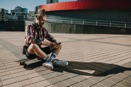 Delighted man sitting on his skateboard in the city