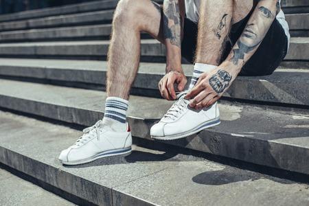 Junger Mann mit Tätowierungen an den Händen, der seine Schuhe bindet