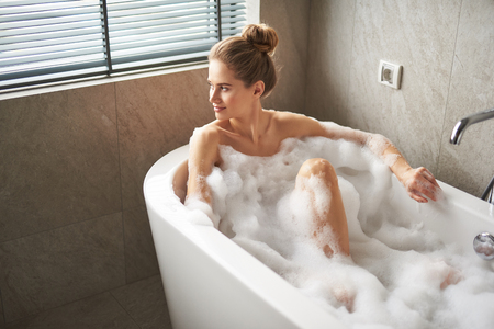 Young lady taking relaxed foam bath at home