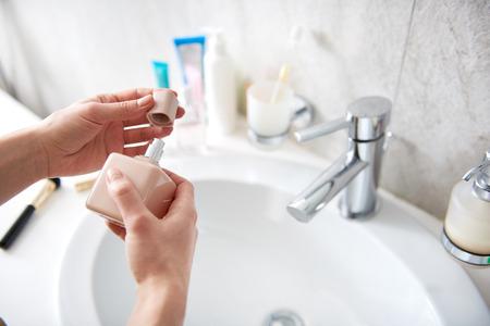 Giovane donna che apre la parte superiore della bottiglia di profumo