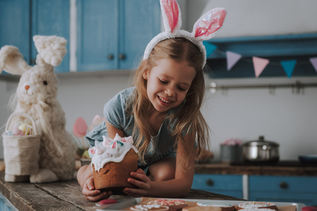 Little happy girl with Easter cake in hand