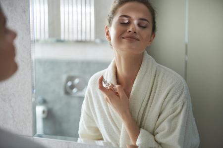 Junge lächelnde Dame, die morgens ihr Parfüm genießt