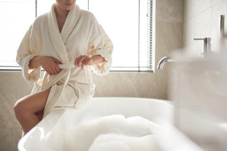 Lady untying belt of bathrobe to take bath Stock fotó