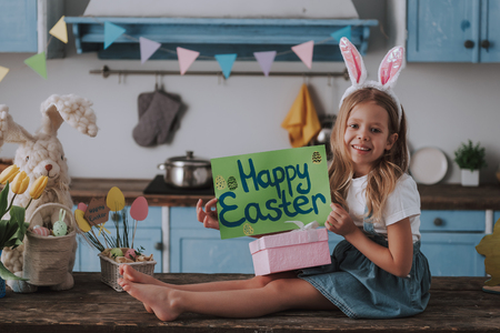 Girl holding poster with Happy Easter greetings Foto de archivo