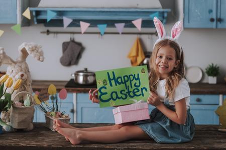 Mädchen, das Poster mit fröhlichen Ostergrüßen hält Standard-Bild