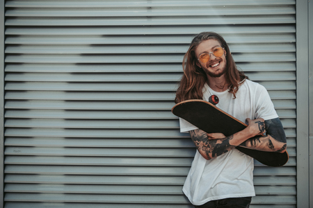 Handsome hipster guy with long hair holding skateboard