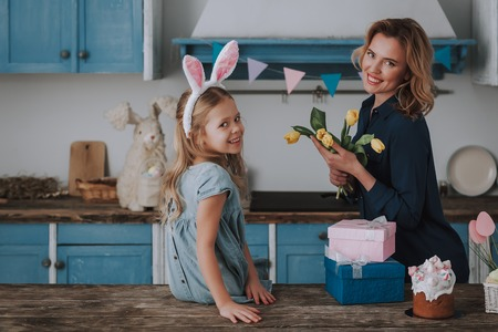Little girl and mom with bunch of yellow tulips
