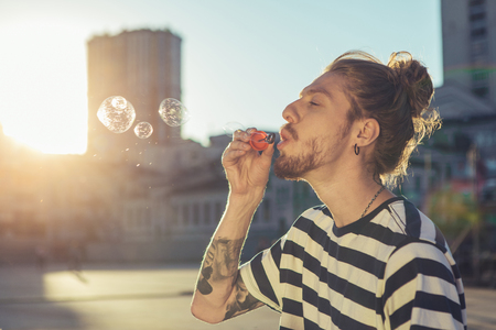 Waist up of a delighted man blowing soap bubbles Imagens