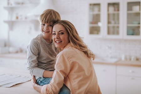 Happy woman hugging her son while being in the kitchen with him