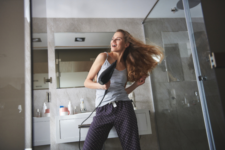 Happy lady having fun while drying hair