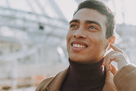 Handsome young man touching wireless earphone and smiling Banco de Imagens