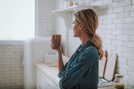 Calm woman holding cup of tea and looking away