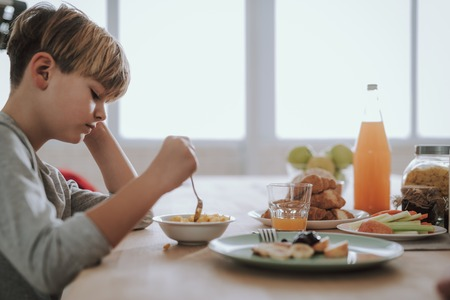 Boy looking at the bowl of cornflakes in front of him Reklamní fotografie