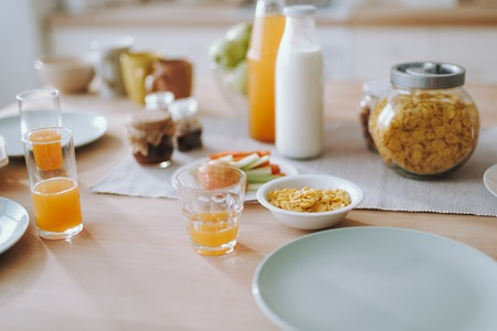 Fresh breakfast. Close up of the table with glasses of orange juice standing next to the empty plates and bowl of corn flakes