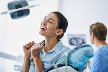Young lady feeling happy while sitting in dental chair