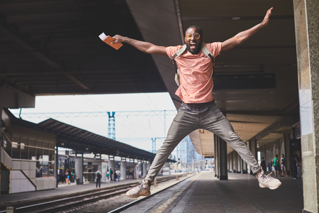 Playful man jumping with happiness before trip