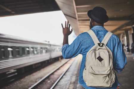 Guy with backpack waving goodbye to train