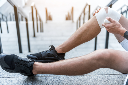 Close up photo of person applying elastic bandage on the leg