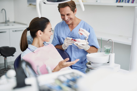 Smiling dentist showing teeth model to young woman Stock Photo