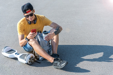 Smiling man sitting on the ground and using modern smartphone