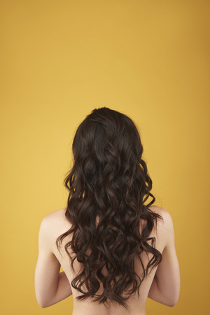 Back side portrait graceful woman with curly hairs Stockfoto