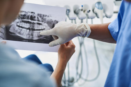 Young lady holding dental x-ray while dentist pointing at it Stockfoto