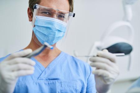 Männlicher Zahnarzt in Schutzmaske mit zahnärztlichen Werkzeugen