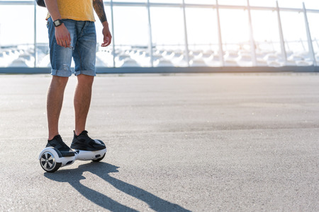 Man in jeans shorts standing on the gyro scooter 스톡 콘텐츠