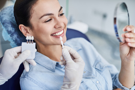 Male dentist comparing color of lady teeth with sample Stock Photo