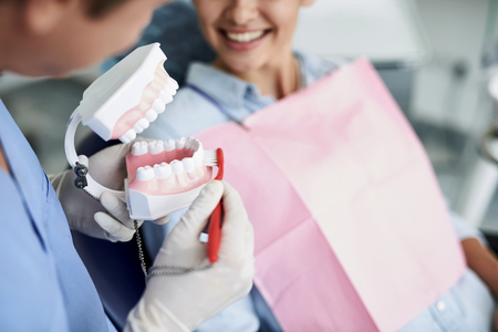 Dentist showing how to clean teeth properly to young lady