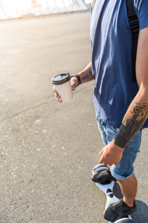 Close up of tattooed man drinking coffee from carton cup