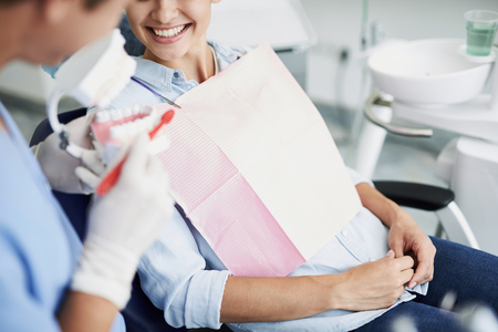 Dentist showing teeth model to smiling young woman