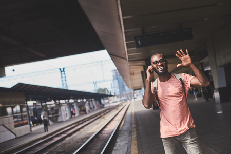 Smiling man on train station talking on phone and waving his hand