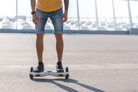 Man in jeans shorts standing on gyro scooter outdoors