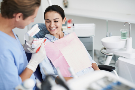 Male dentist showing teeth model to smiling young lady