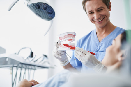 Cheerful dentist showing how to brush teeth properly to young woman