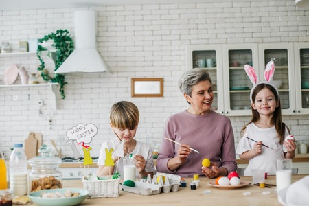 Waist up portrait of happy children and their grandmother coloring Easter eggs Stock Photo - 119179155