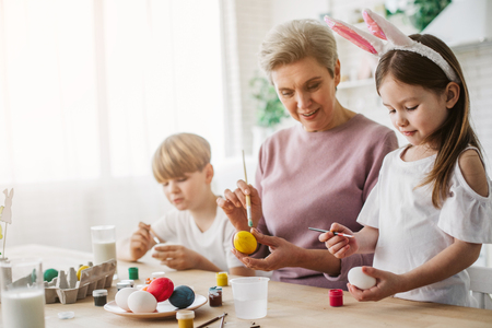 Beautiful grandmother and her granddaughter painting Easter eggs at home Stock Photo - 119179158