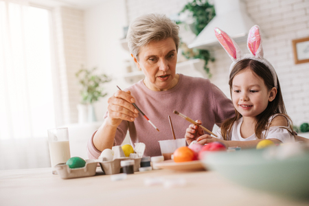 Cropped photo of gray-haired woman talking to little girl at table