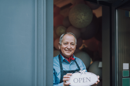 Joyful old man standing in the doorway of cafe and holding open sign Foto de archivo