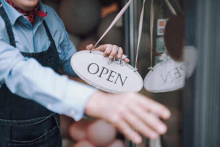 Cafe owner holding open sign and opening door