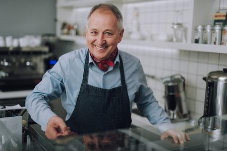 Handsome gentleman in apron standing behind the counter
