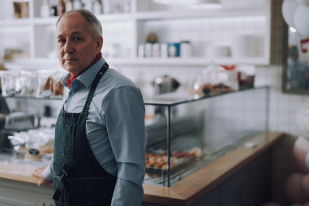 Good-looking senior man standing near glass showcases in his shop