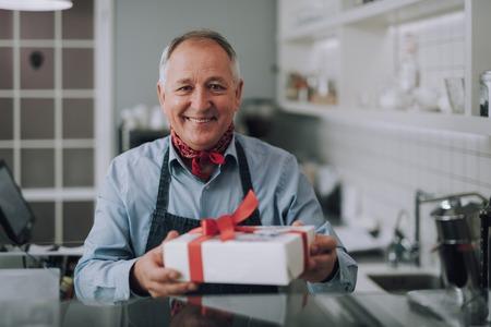 Joyful gentleman with present standing behind the counter