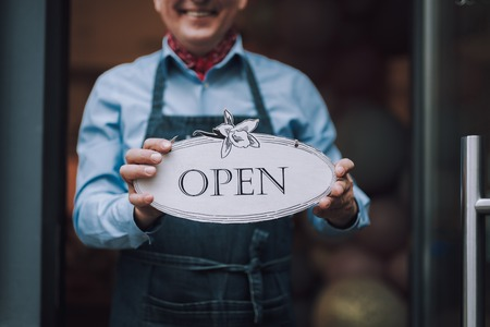 Cheerful gentleman in apron holding open sign